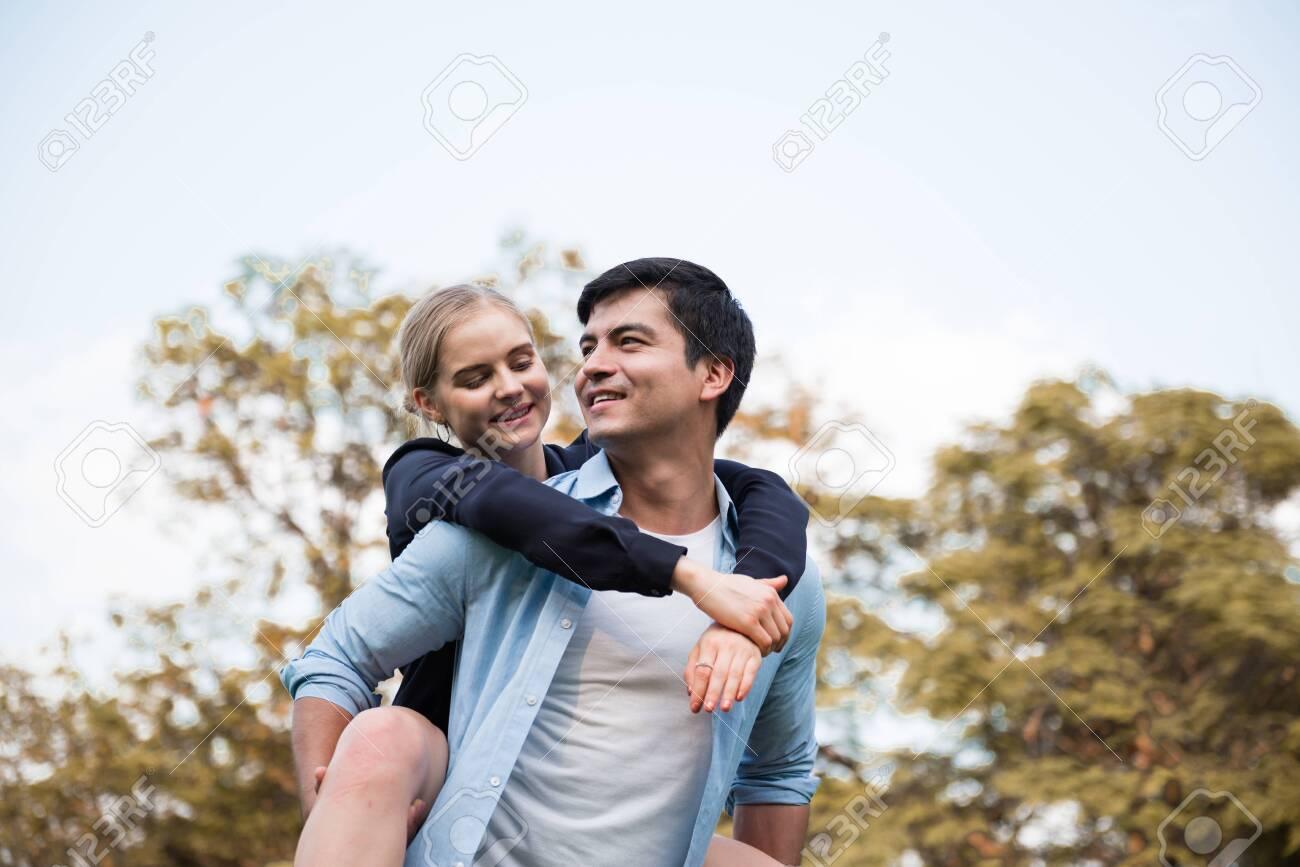 Boyfriend carrying his girlfriend on piggyback. - 148628566