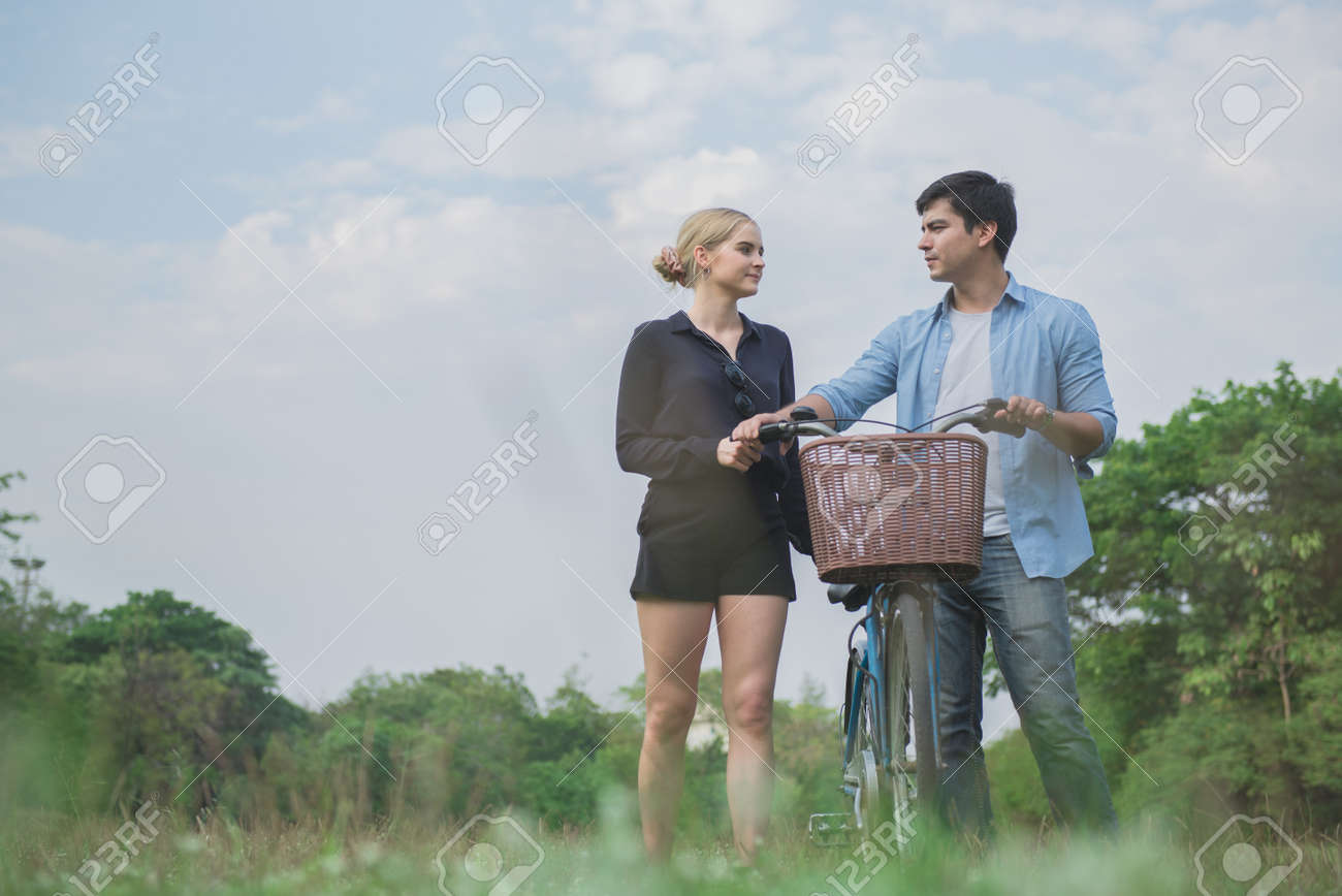 Young couples holding hands and walking on the grass in the park - 148628577