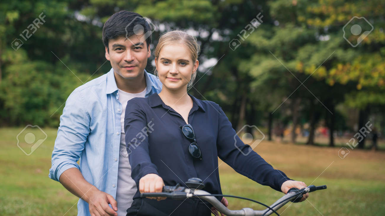 active couple together enjoying romantic walk with bicycle in park - 148566772