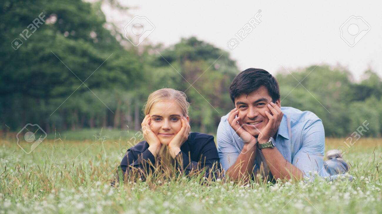 Lovely couple laying down on the green grass - 148606121