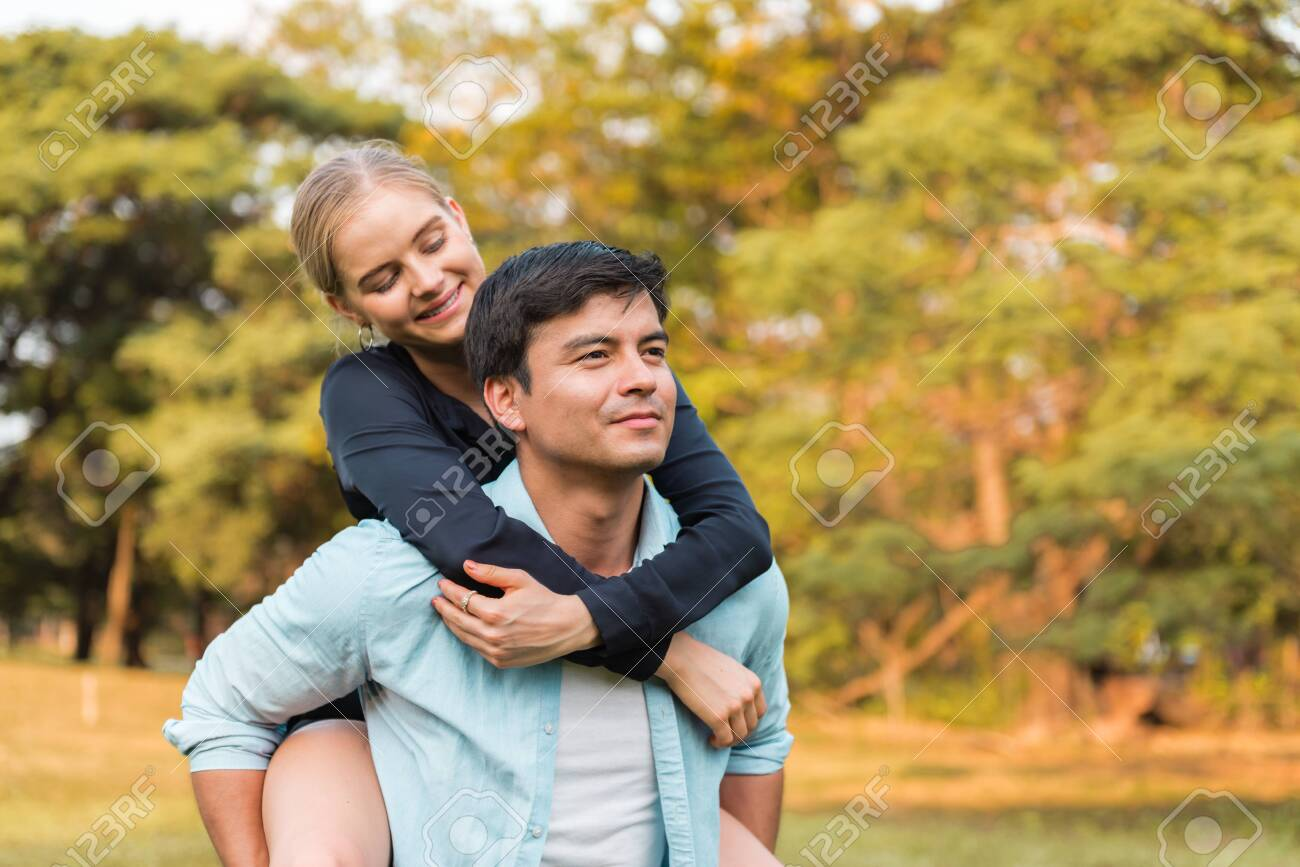 Coupe in park. Boyfriend carrying his girlfriend on piggyback. - 148724594