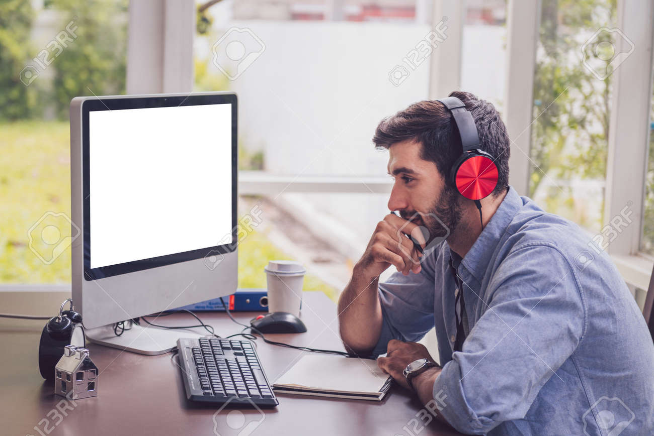 Confident young man working and concentrate on monitor while sitting at his working place in office - 148725208