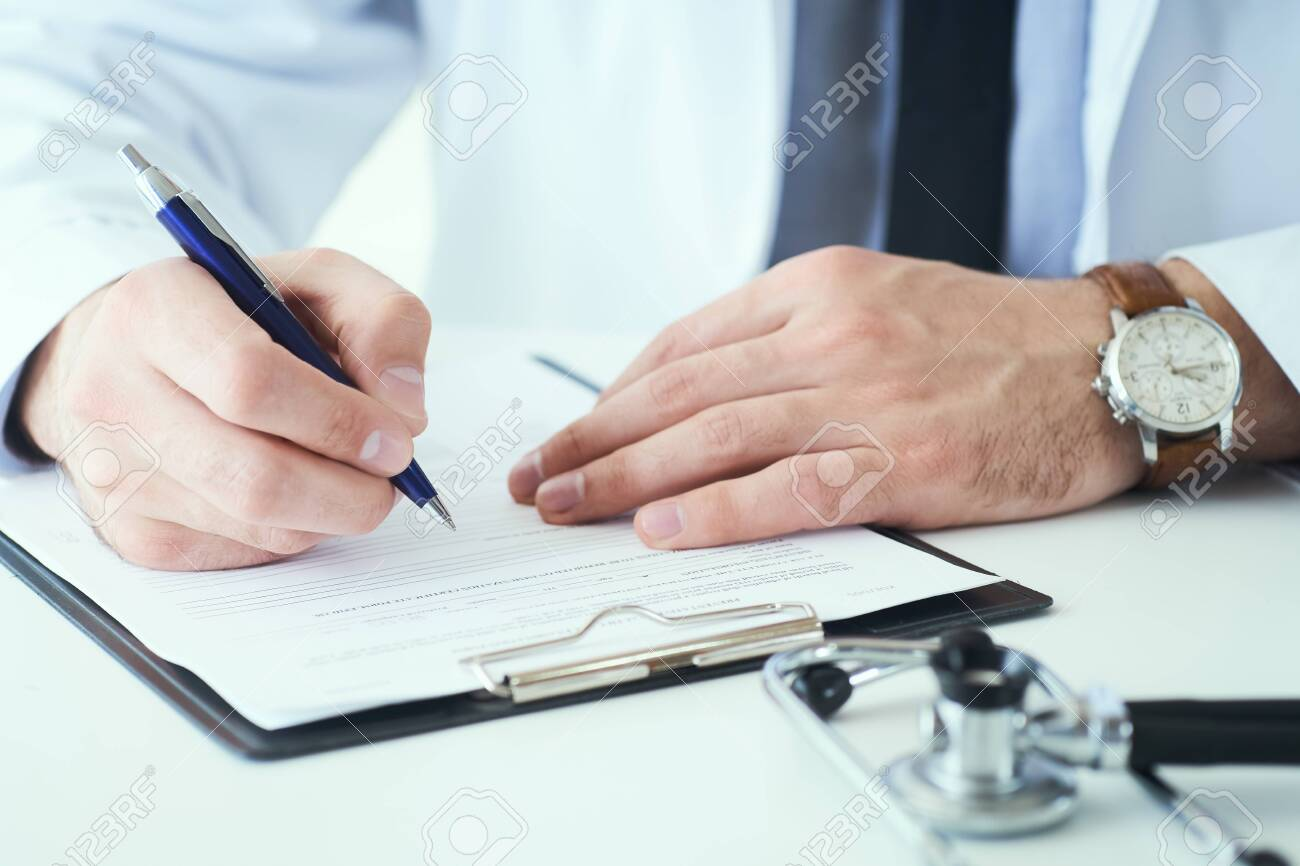Mid section of male doctor writing write prescription to patient at worktable. Panacea and life save, prescribing treatment. - 130355641
