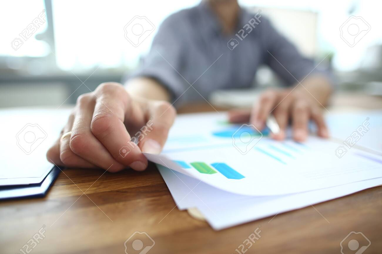 Close up of young businessman holding paper with financial information, editing documents, explaining marketing strategy or planning company economic growth at brainstorming meeting at office. - 134821466
