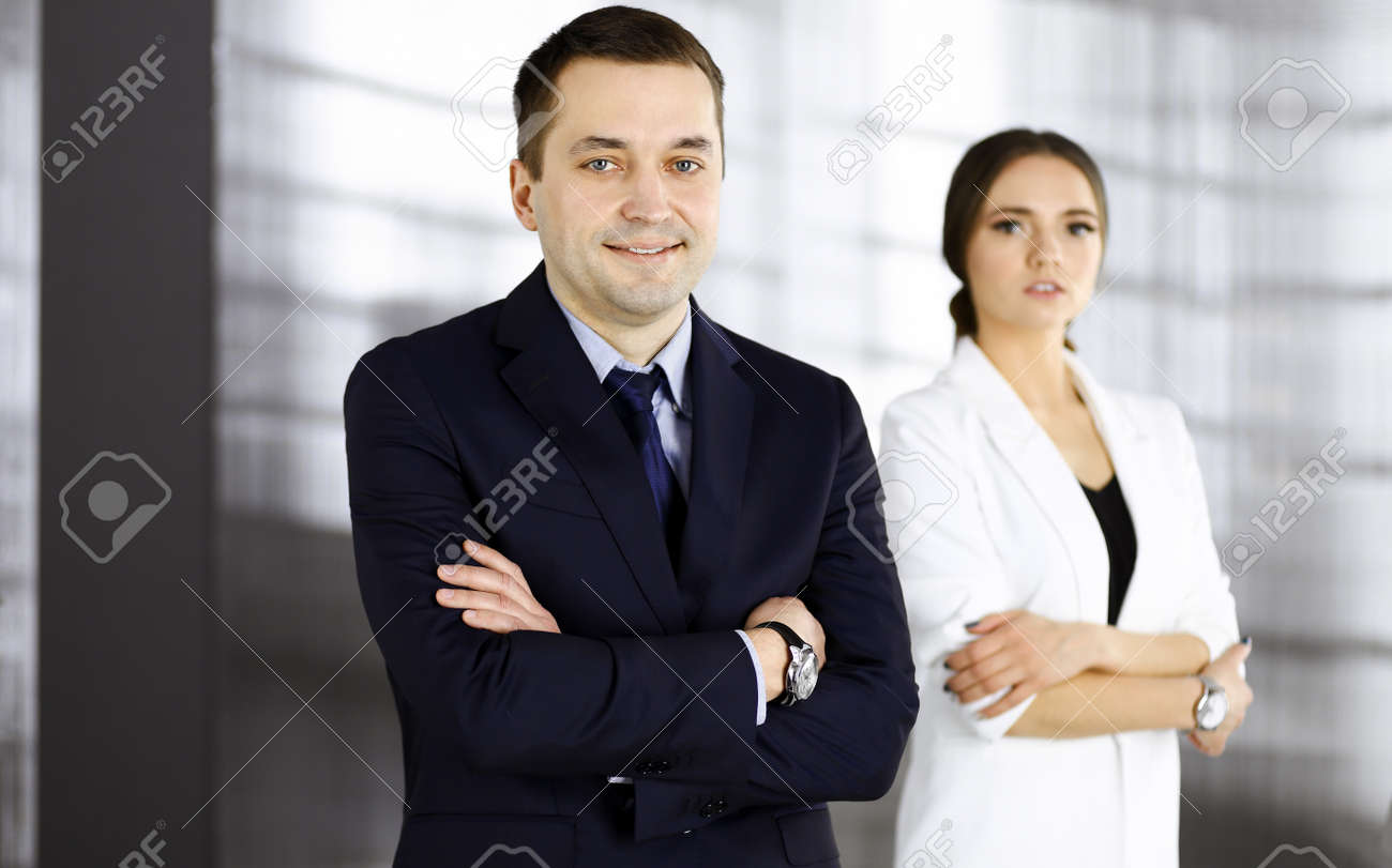 Portrait of a friendly middle aged businessman in a dark blue suit, standing with crossed arms together with a colleague in a modern office. Concept of success in a business - 158137880