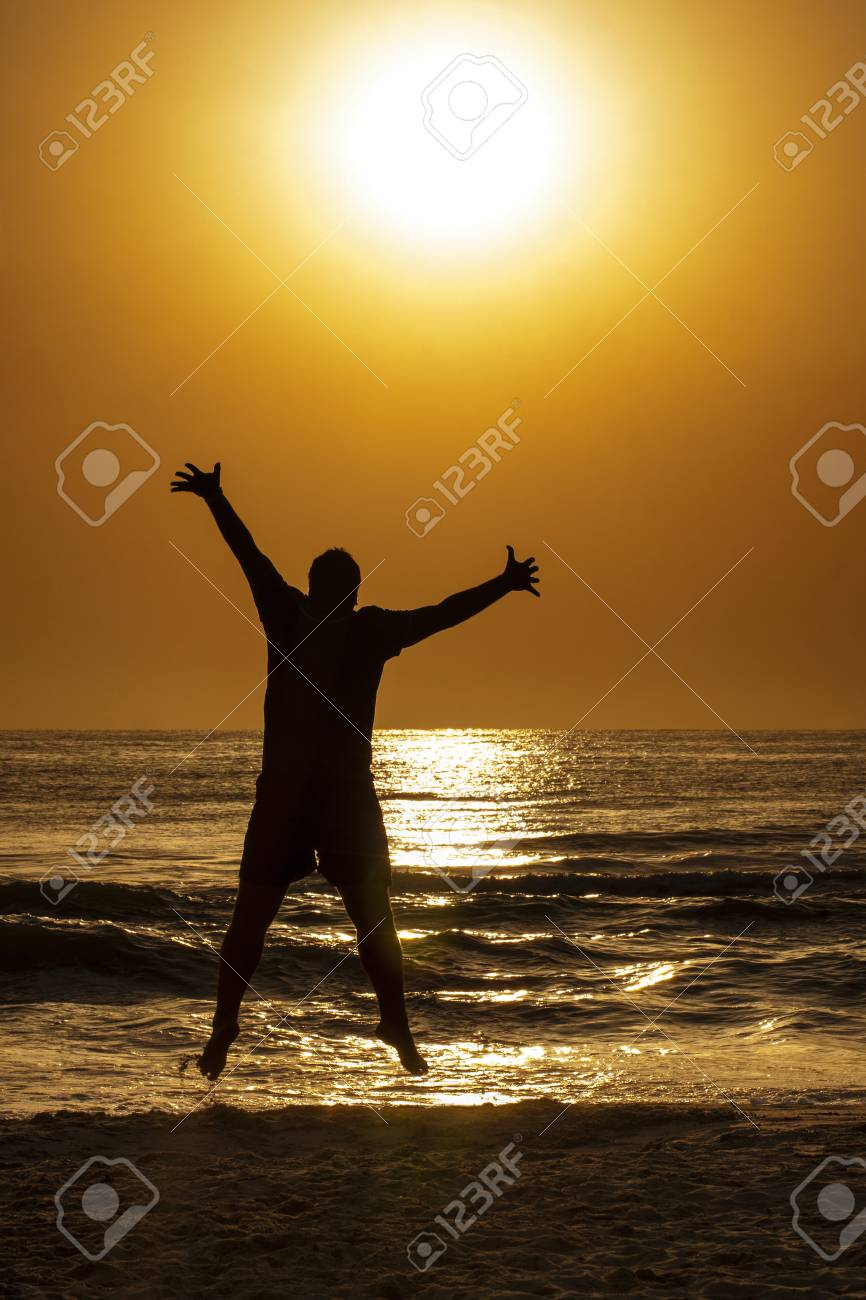 d2c9b1bd9dc Silhouette of young man jumping on the beach to embrace the Sun Stock Photo  - 53633150