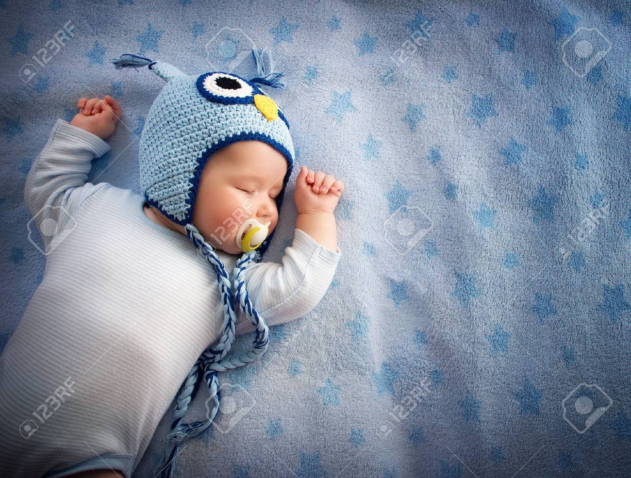 4 month old baby in owl hat sleeping on blue blanket Stock Photo - 37732546 cb2d07da971