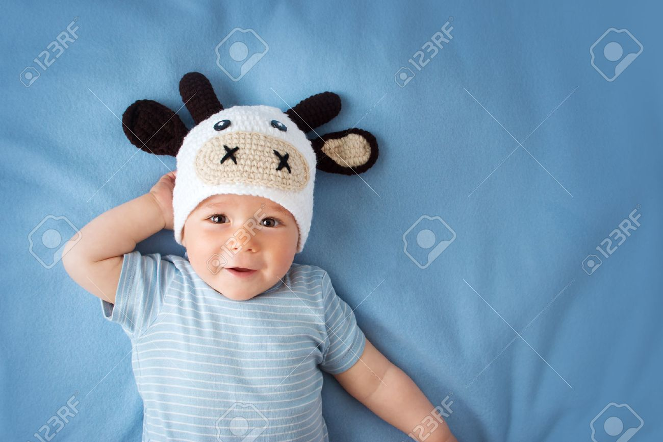 cute baby in a cow hat on blue blanket Stock Photo - 44080368