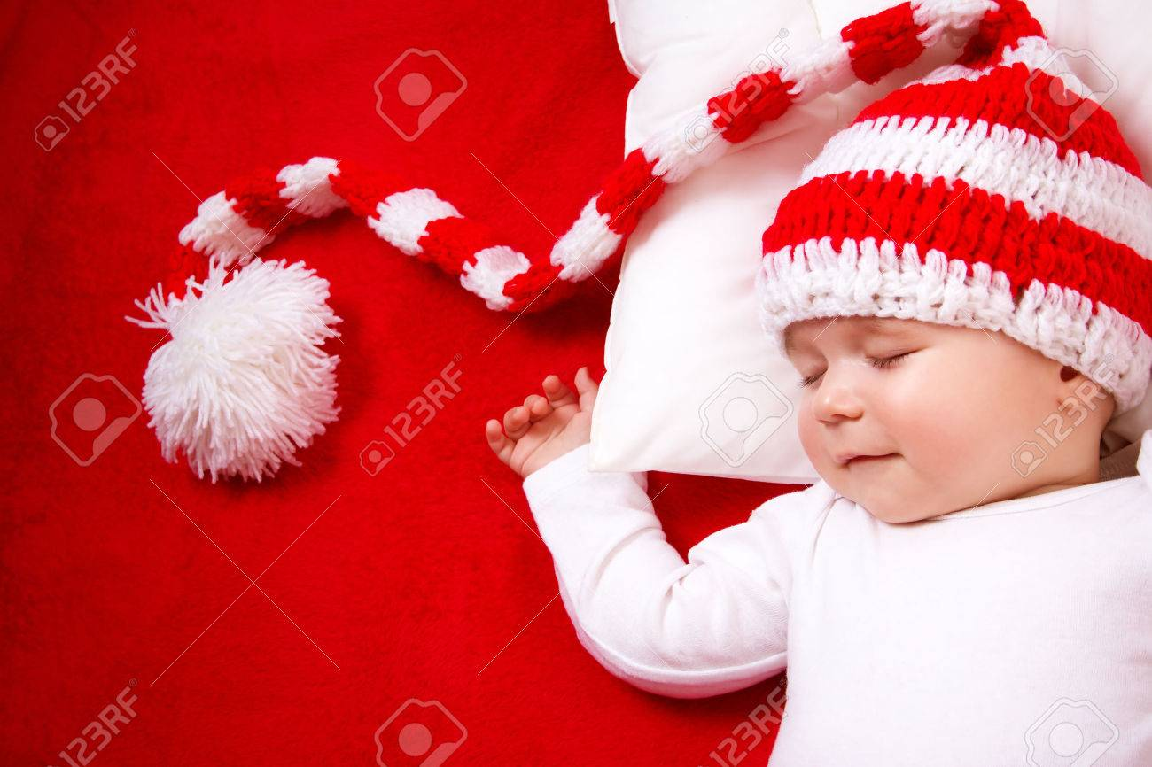 Sleepy baby on red blanket in knitted hat Stock Photo - 45388965