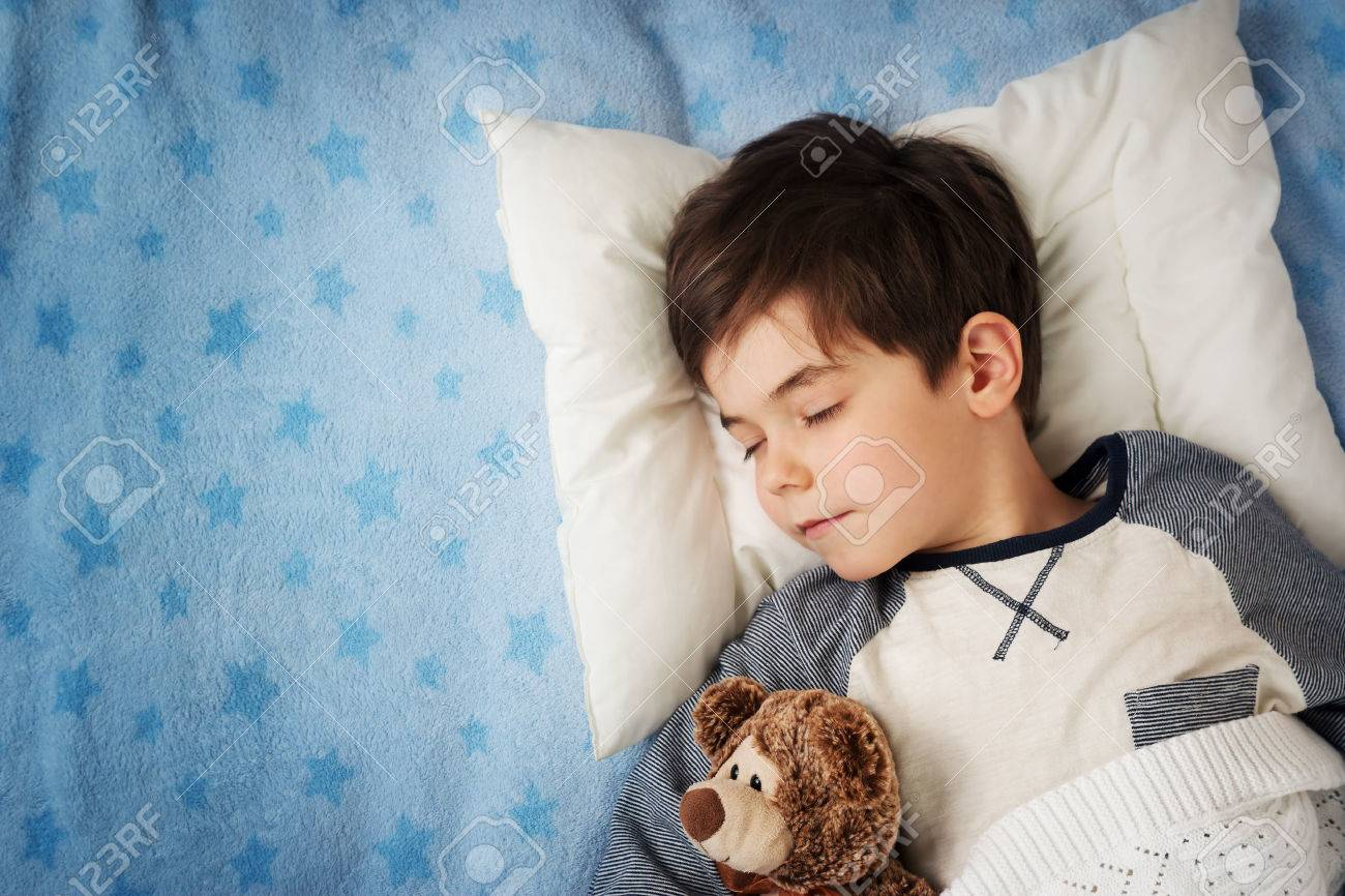 six years old child sleeping in bed on pillow with alarm clock and a teddy bear - 50556434