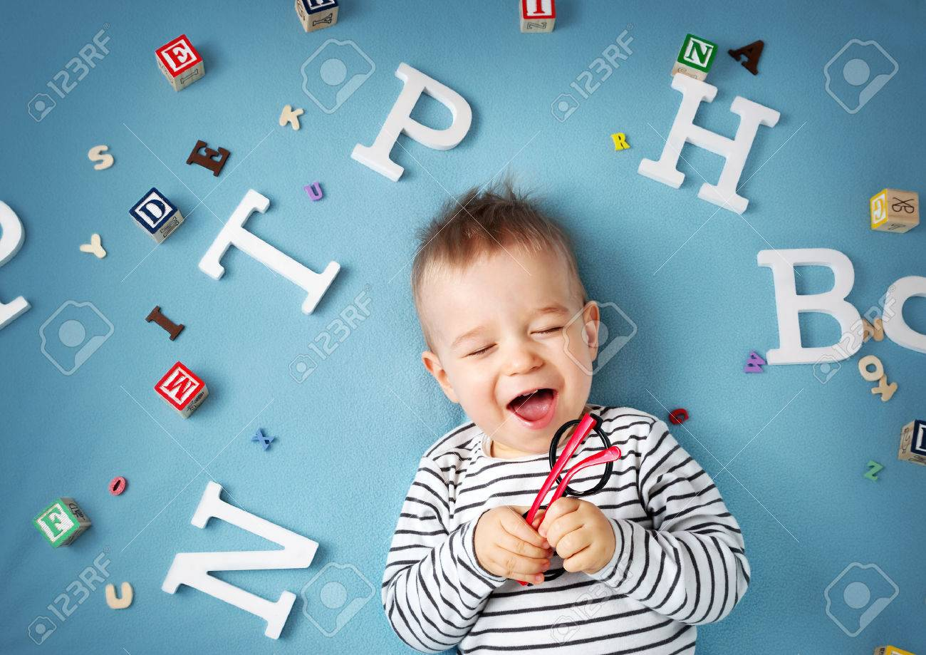 One year old child lying with spectacles and letters on blue background - 56033302