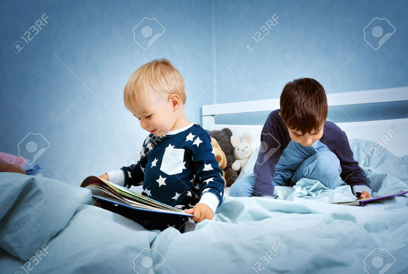 Brothers sitting in the bed in pyjamas and reading books - 63246250