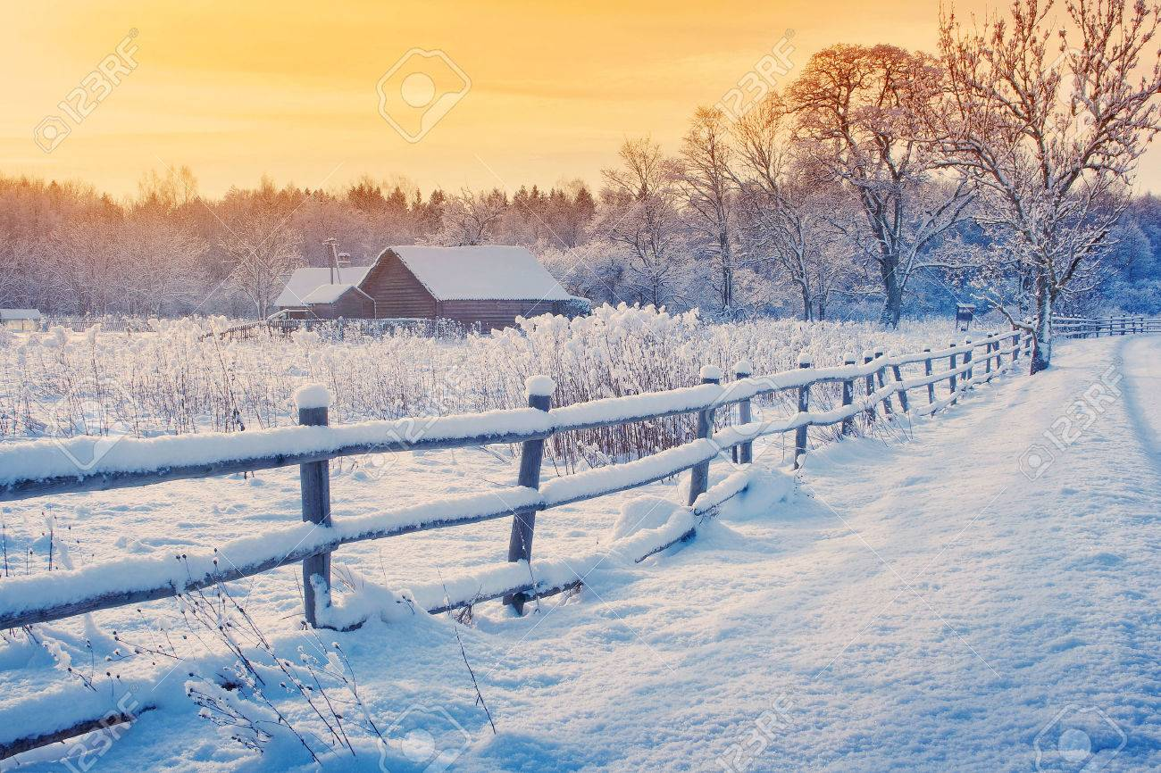Rural house with a fence in winter. Village after snowfall - 63246277
