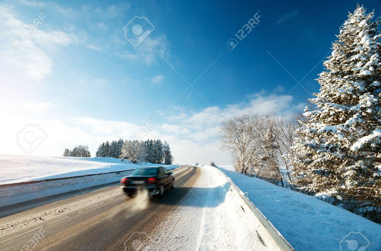 Car tires on winter road covered with snow - 66129480