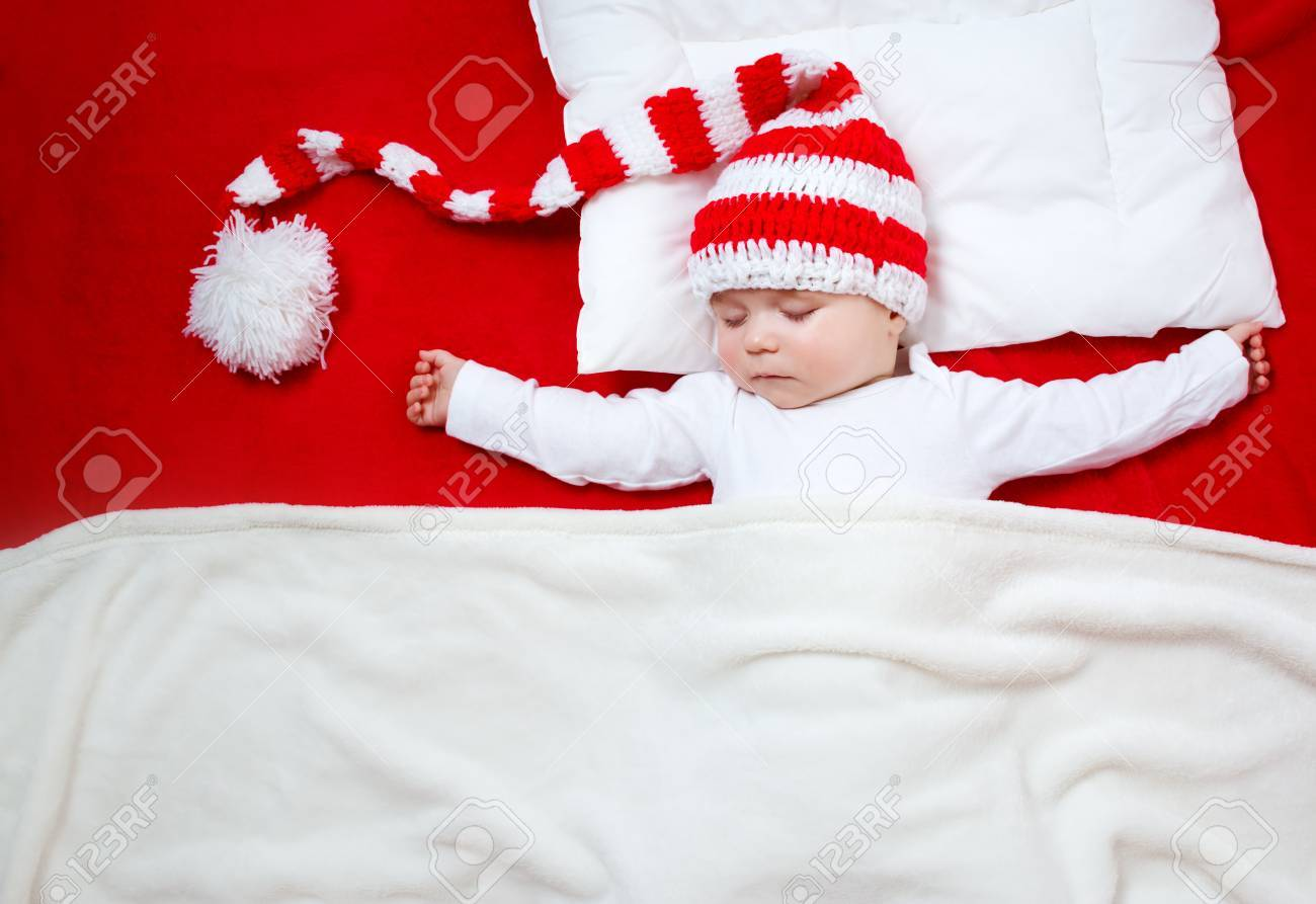 59f1140278c Sleepy baby on red blanket in knitted hat. Cute child sleeping in christmas  cap Stock