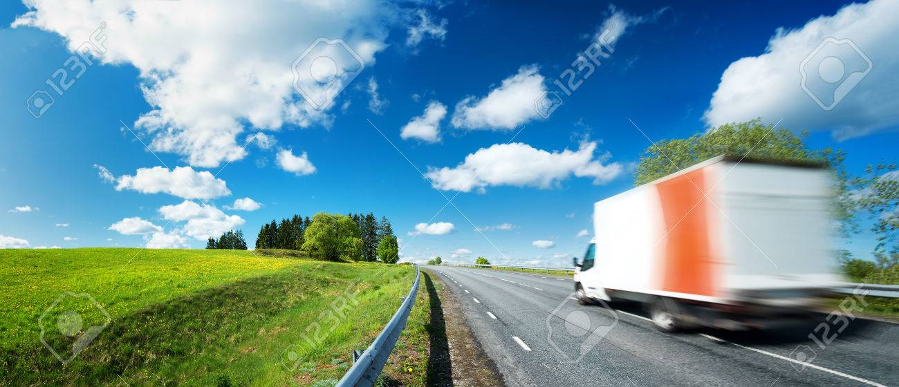 asphalt road on dandelion field with a small truck. van moving on sunny day - 66130857