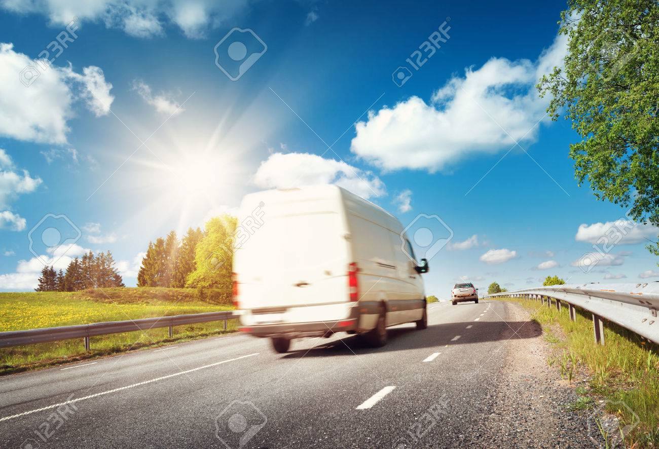 asphalt road on dandelion field with a small truck. van moving on sunny day - 66130870