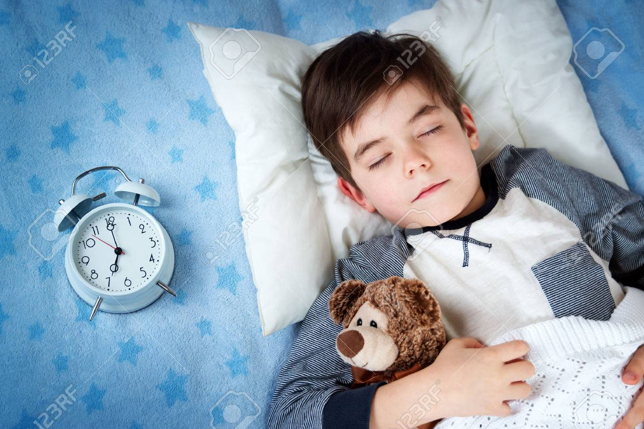 six years old child sleeping in bed on pillow with alarm clock and a teddy bear - 66539976