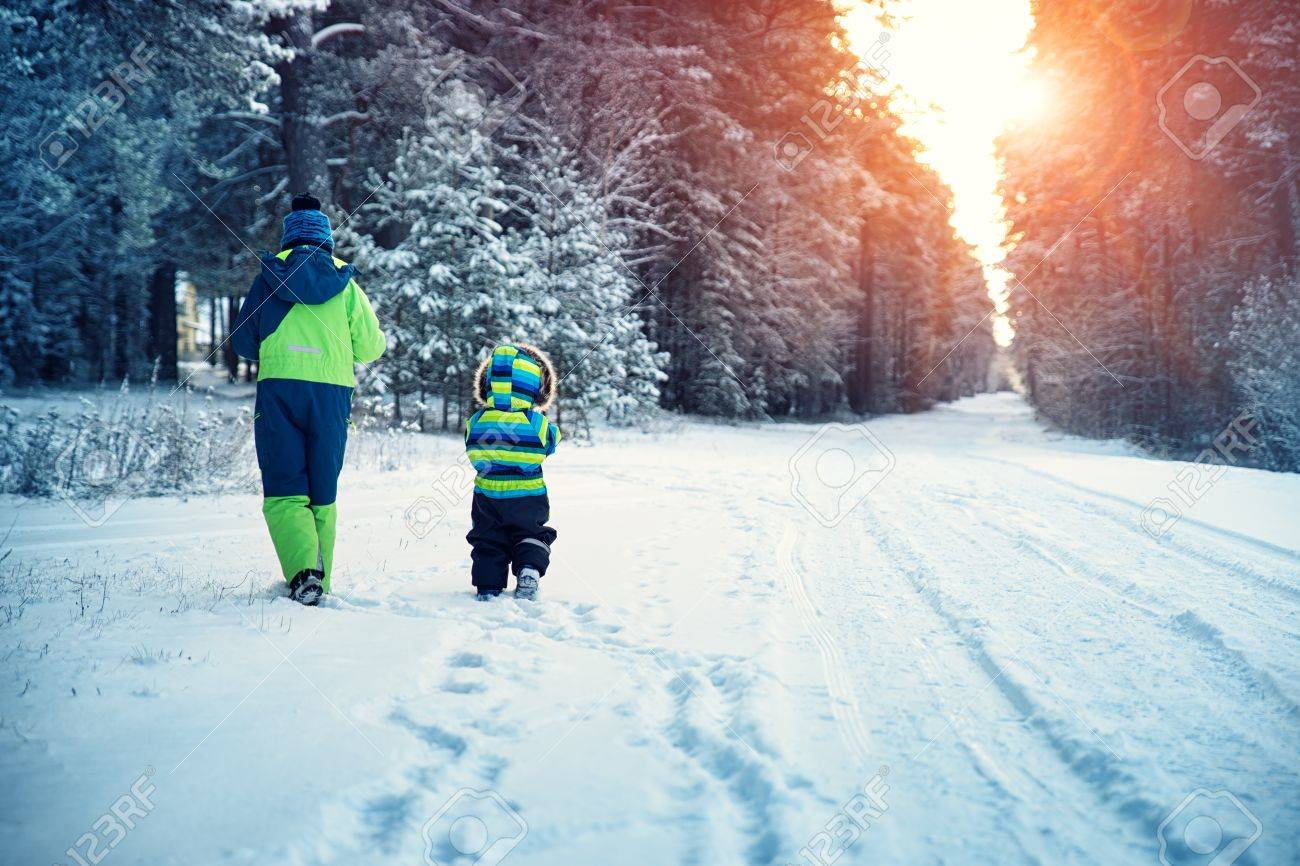 66118aa197461 Children walking on snow at snowfall. Boys in winter clothes outdoors in cold  weather Stock