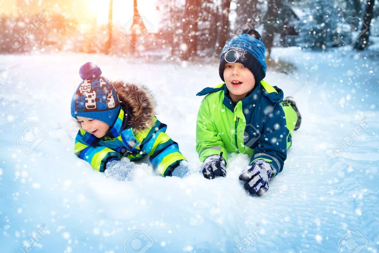 8d2308d80c022 Children playing in snow at snowfall. Boys in winter clothes outdoors in cold  weather Stock