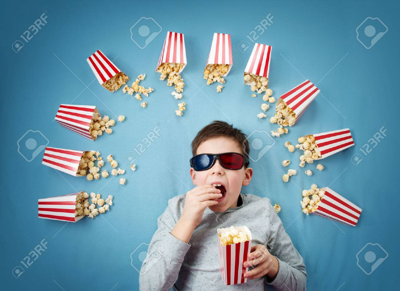 Child lying on blue background in 3d glasses and watching tv - 69914395