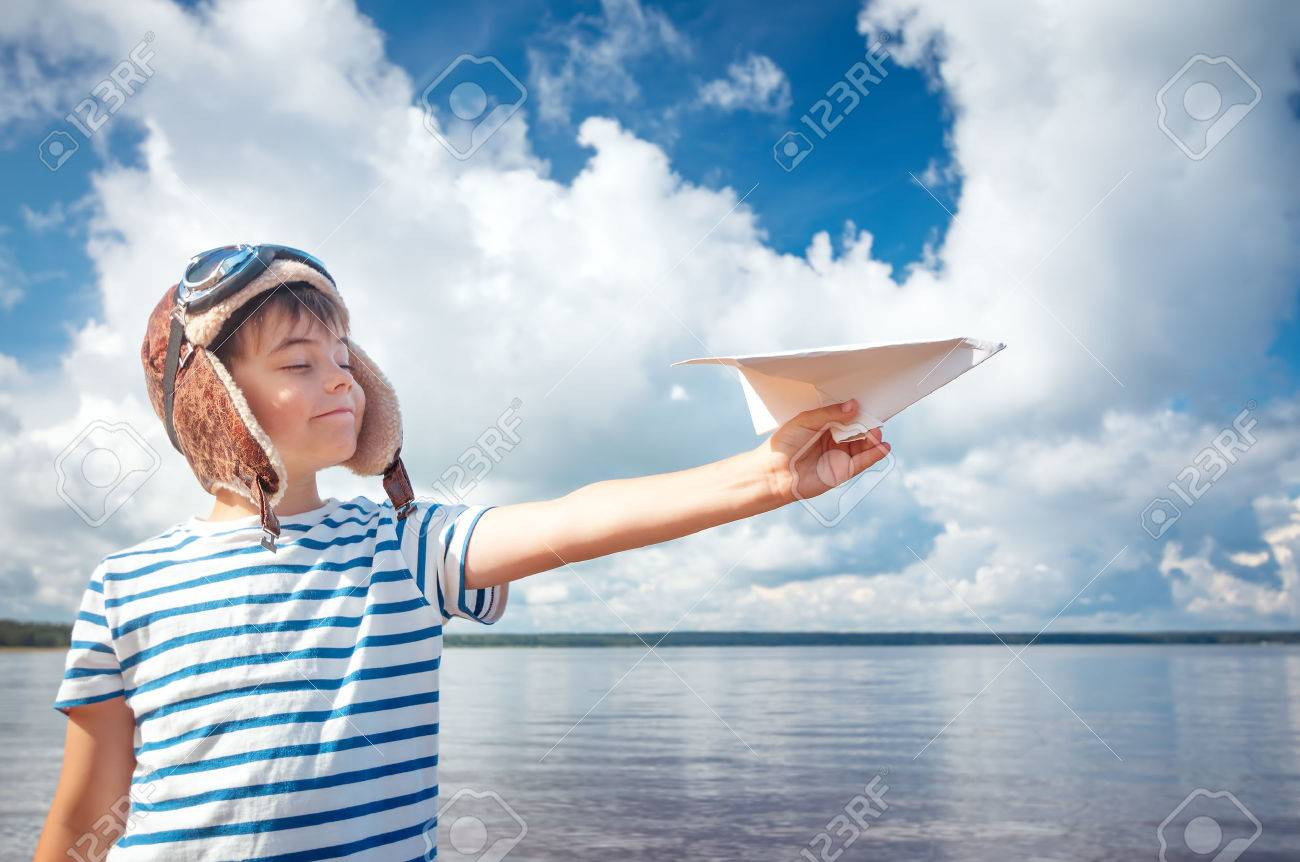 boy playing with a paper plane in aviator hat - 71054301