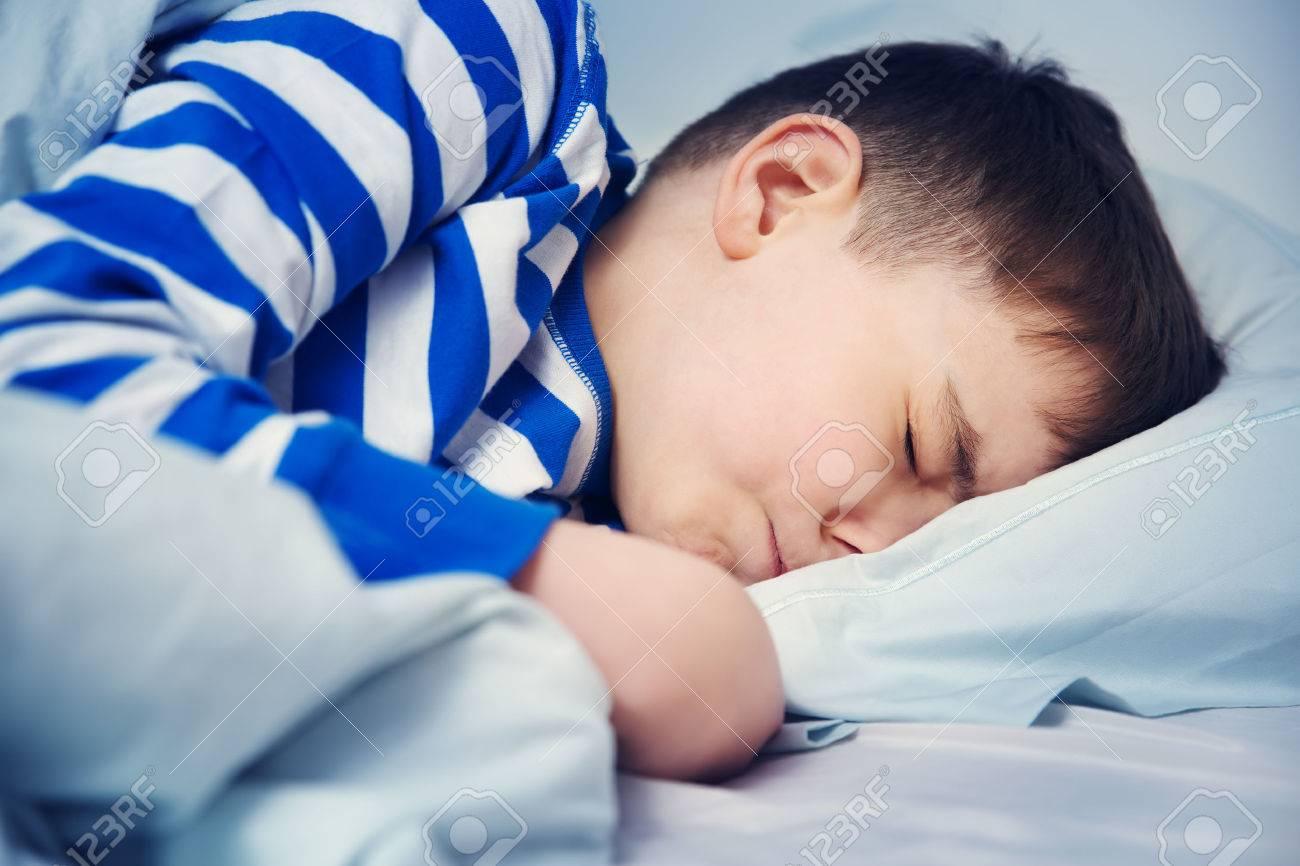 Boy sleeping in bed in pajamas - 75938118