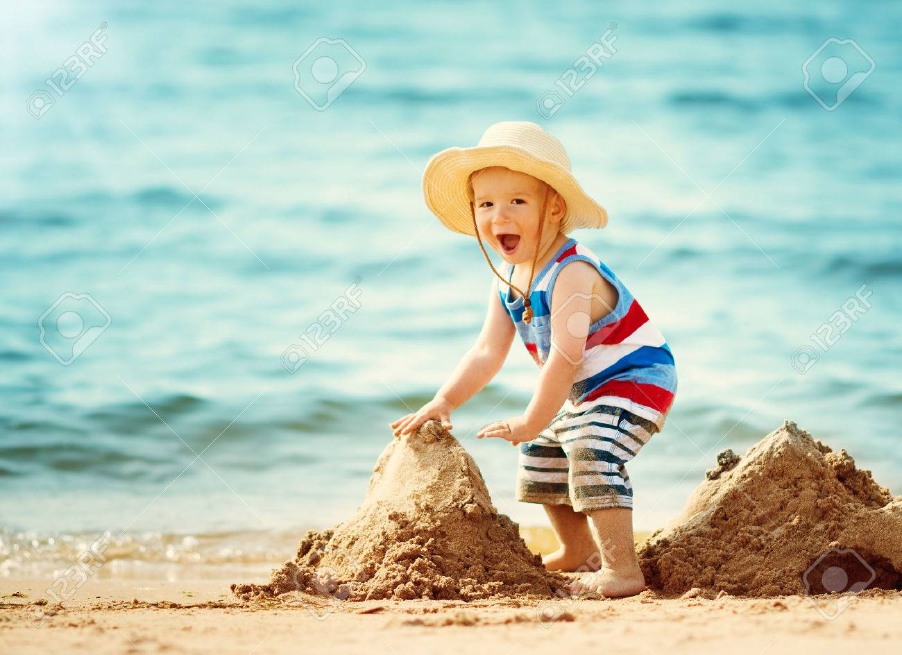 little boy walking at the beach in straw hat - 76196908
