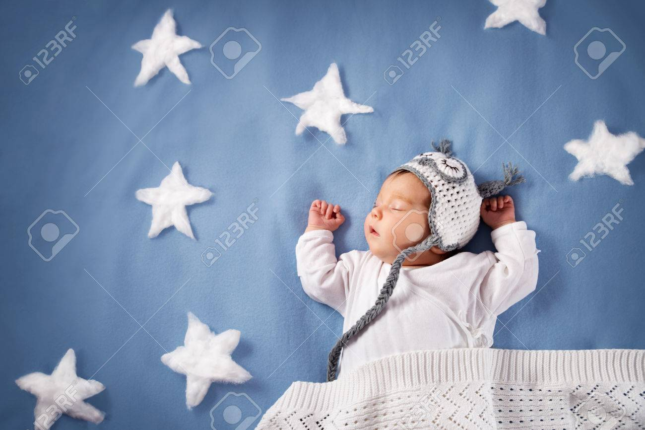 Cute newborn baby girl lying in the bed. 2 month old child in owl hat sleeping on blue blanket - 76556170