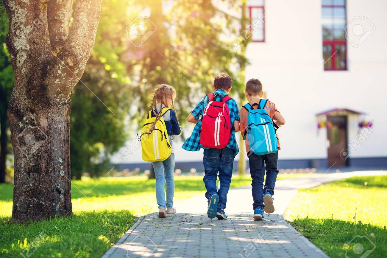 Children with rucksacks standing in the park near school - 80651073