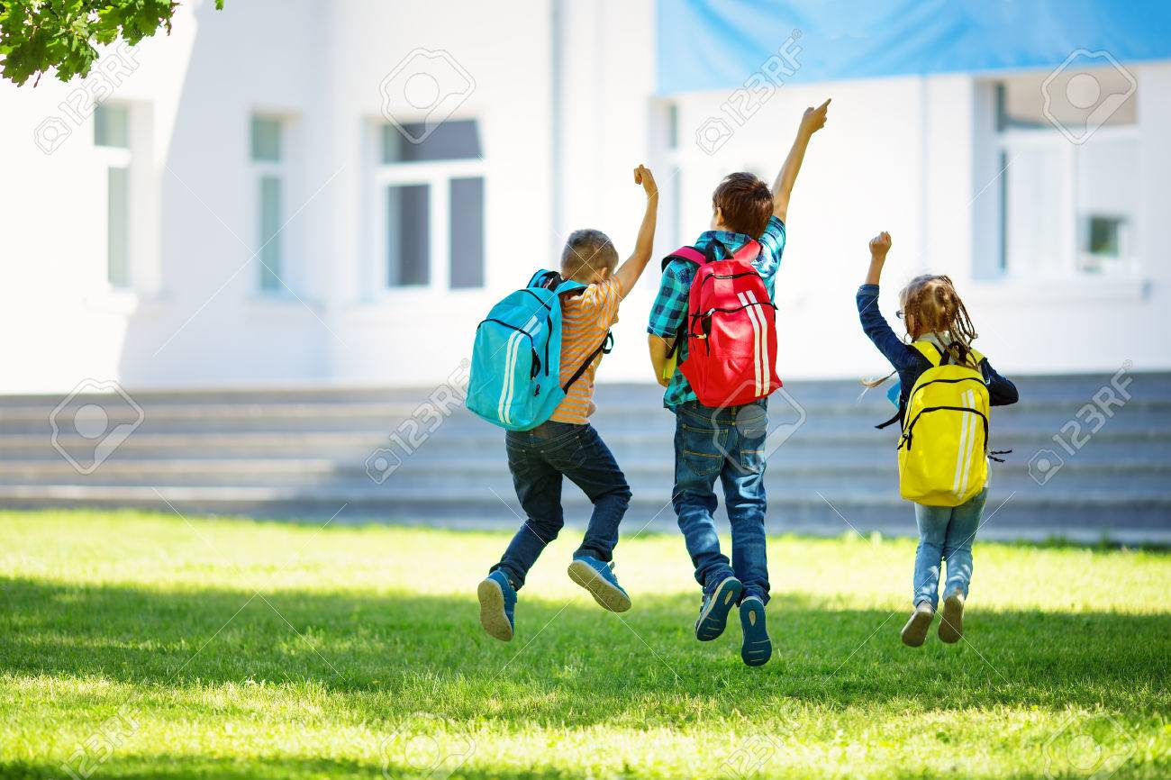 Children with rucksacks jumping in the park near school - 80912783