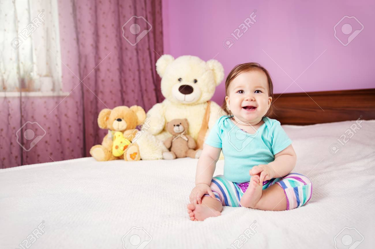Cute Smiling Little Baby Girl Sitting On The Bed With Soft Toys