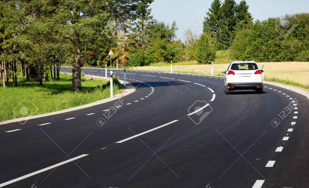 Car on asphalt road in beautiful spring day - 95587262