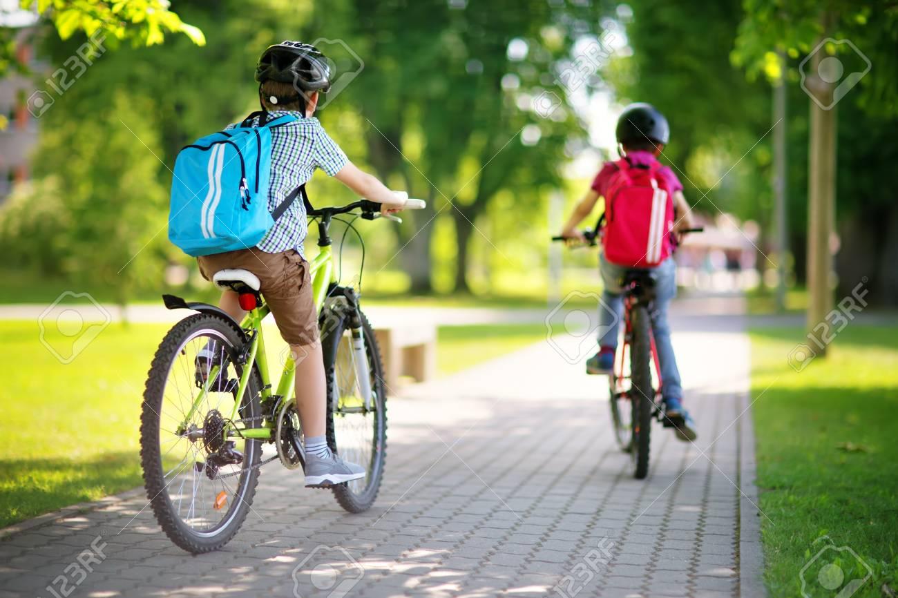 Children with rucksacks riding on bikes in the park near school - 104771129