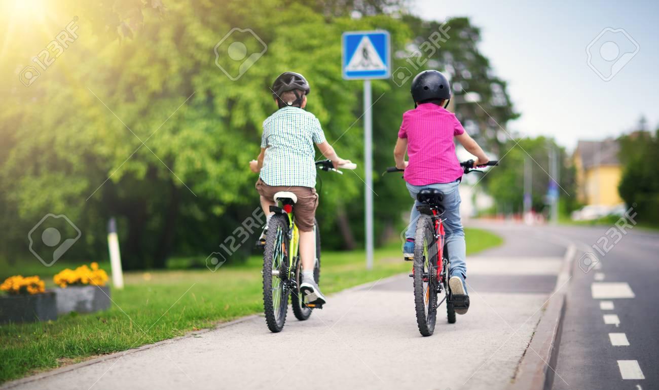 Children with rucksacks riding on bikes in the park near school - 105317248