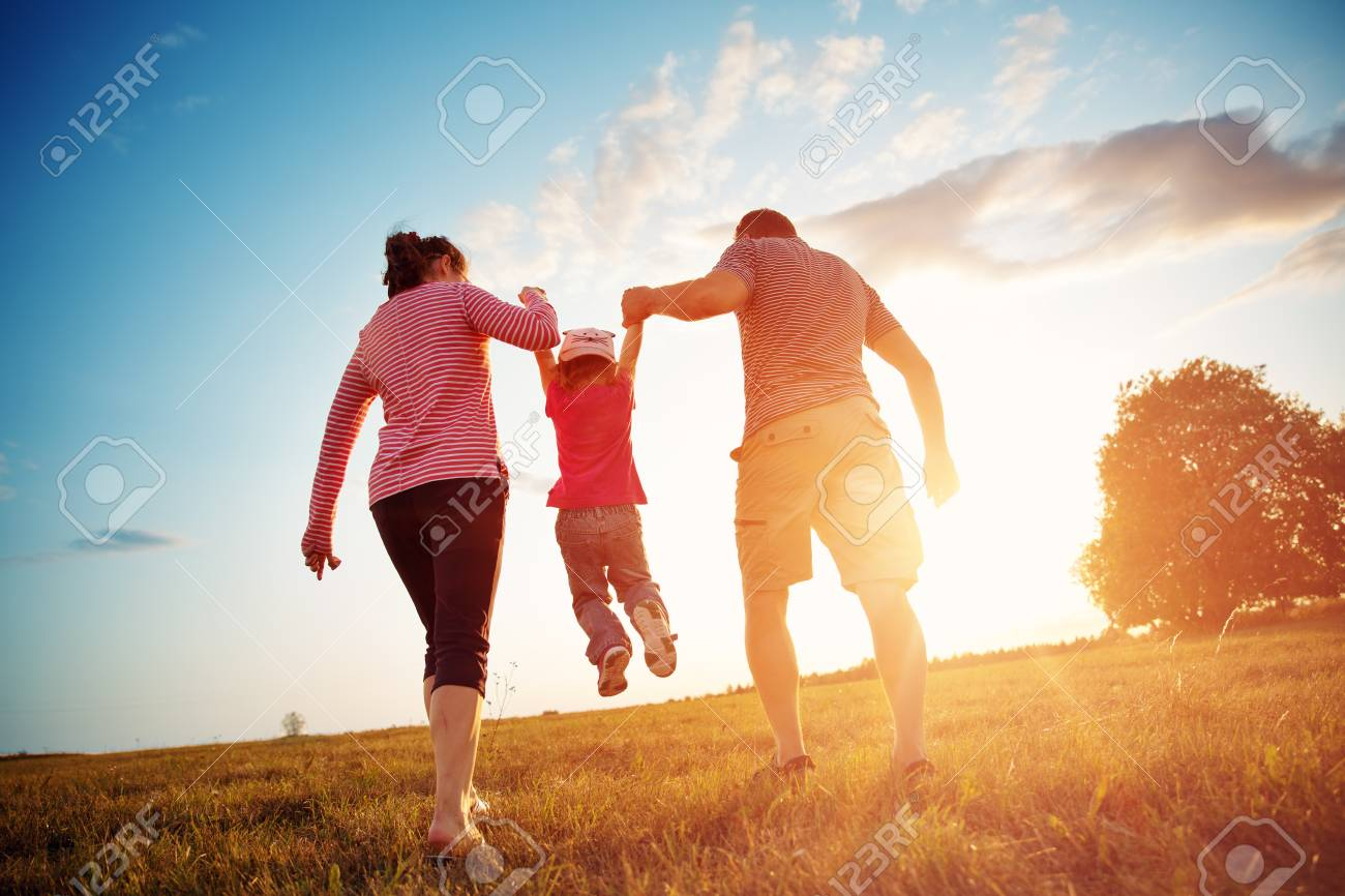 girl with mother and father holding hands on the nature - 106751799