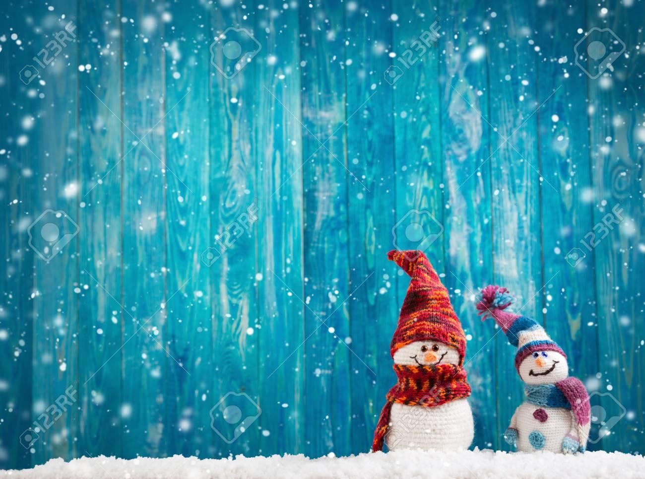 little snowmans on soft snow on blue background - 108096562