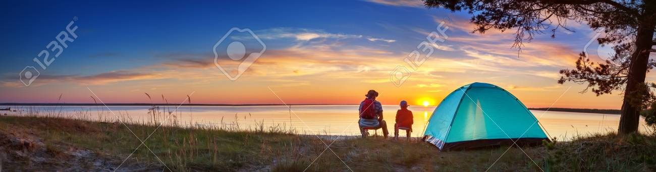 Family resting with tent in nature at sunset - 118718212