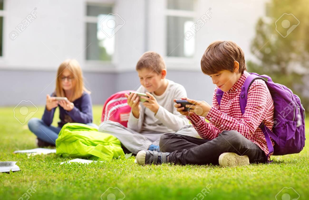Children with rucksacks sitting in the park near school - 129622910