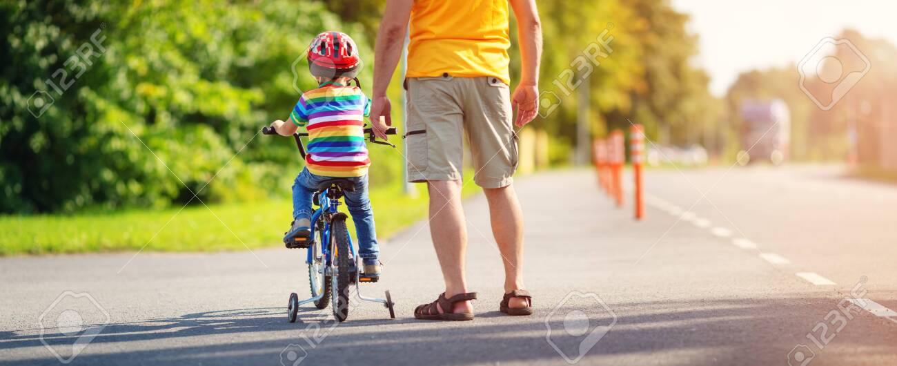 a child on a bicycle in helmet with father on asphalt road - 137893741