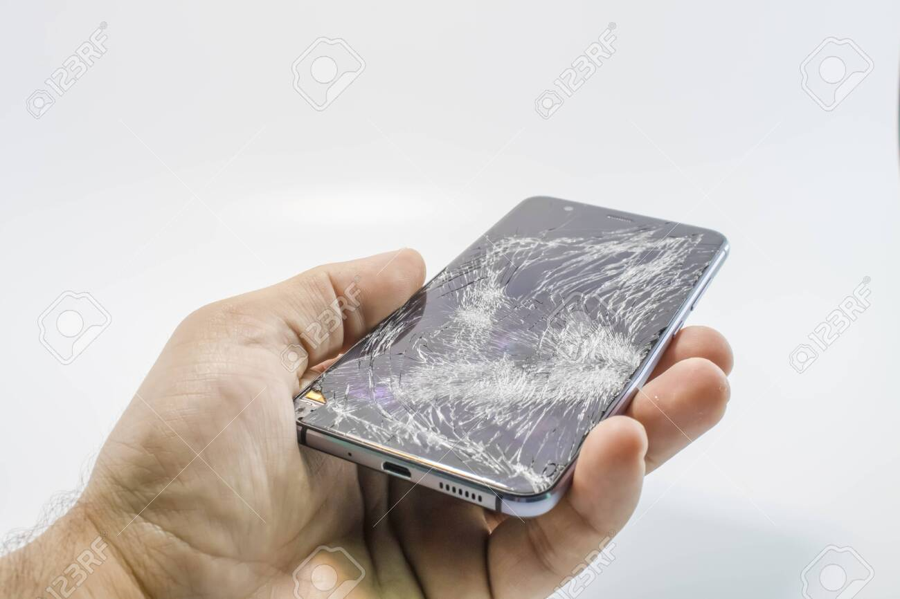 Broken glass mobile phone. It stands in your hand. White background. - 124567293
