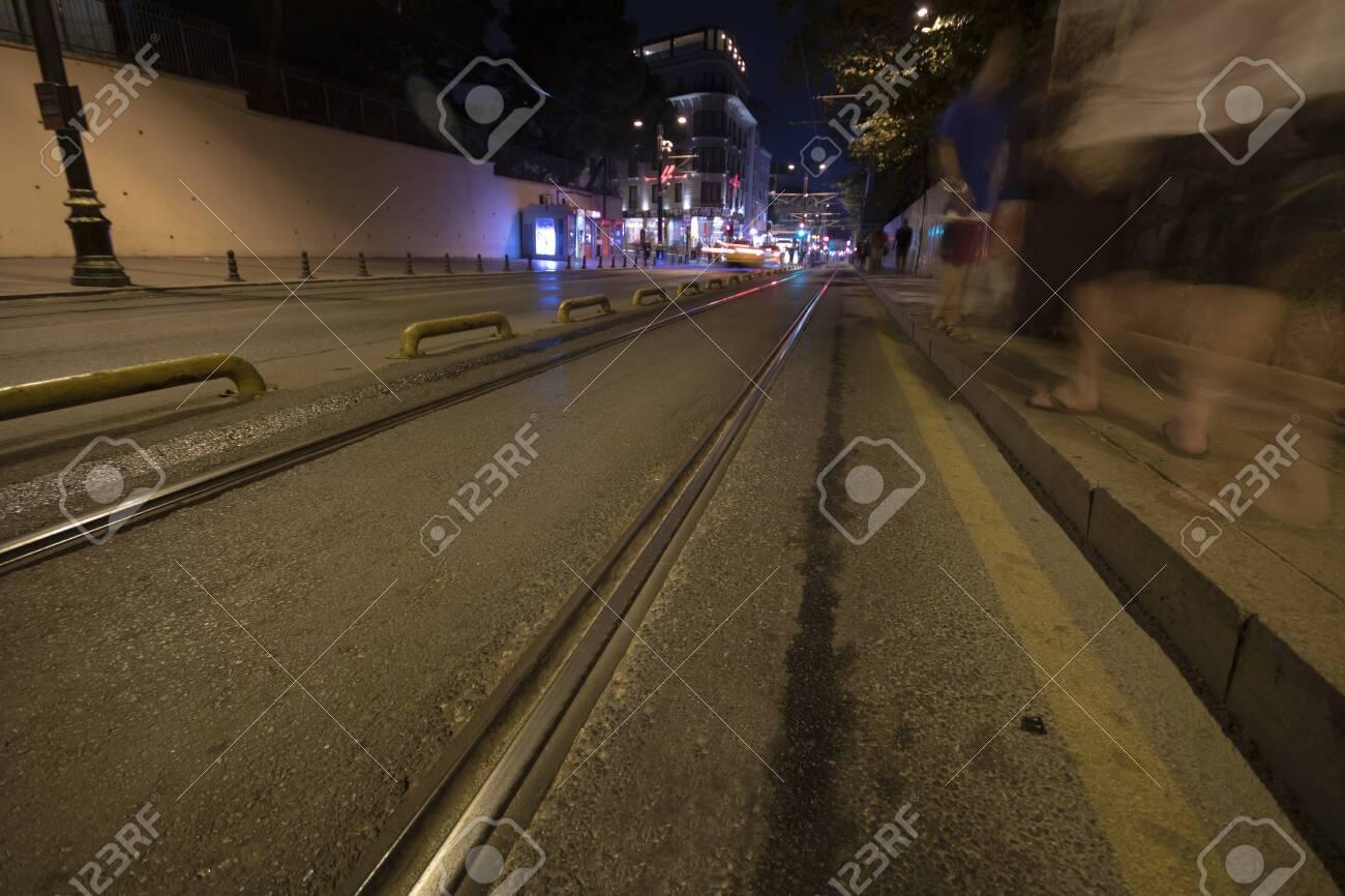 Tram rails on asphalt. People walking and traffic lights on the sidewalk. Filmed at night with long exposure. - 133092983