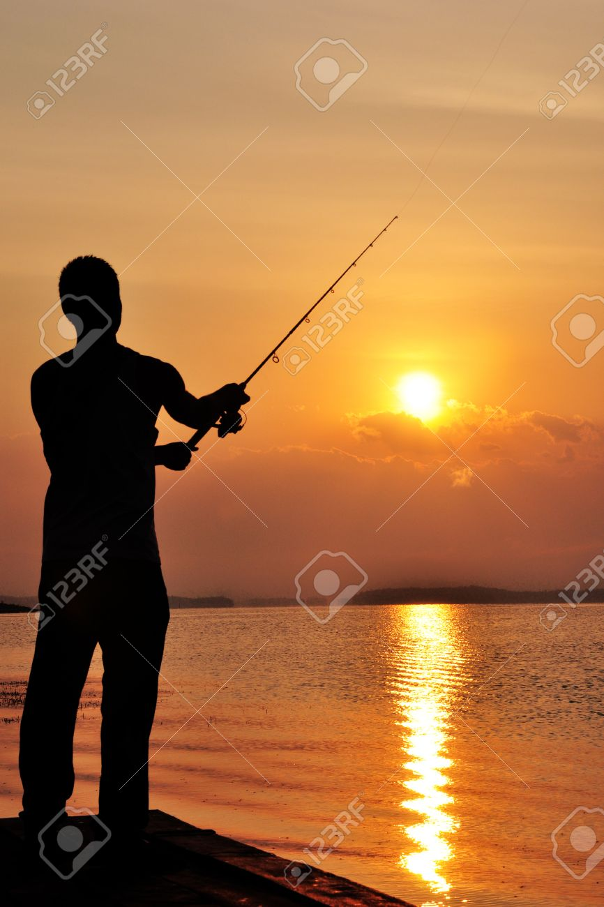 Silhouette of man fishing off the dock at sunset - 24774928