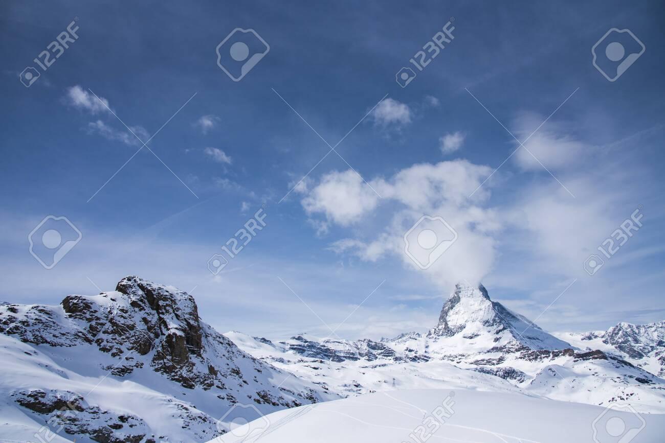 The famous mountain Matterhorn peak with cloudy and blue sky from Gornergrat, Zermatt, Switzerland - 124002315