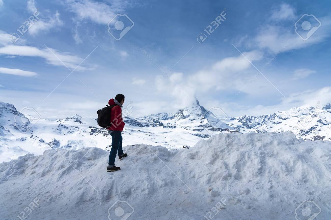 Man in red jacket is looking Matterhorn peak on Gornergrat peak, Zermatt, Switzerland - 131648574