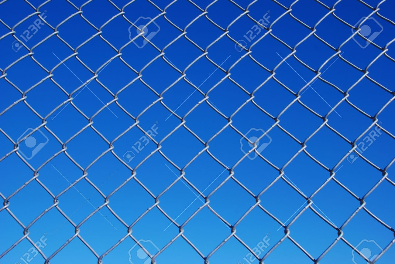 chain link fence with background sky from light to dark blue stock