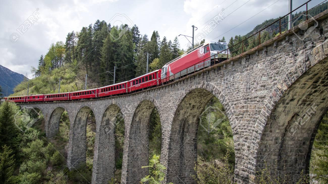 Albula - Switzerland - May 2017: Glacier train on famous landwasser Viaduct bridge.The Rhaetian Railway section from the Albula - Bernina area, Switzerland, Europe. - 93106503