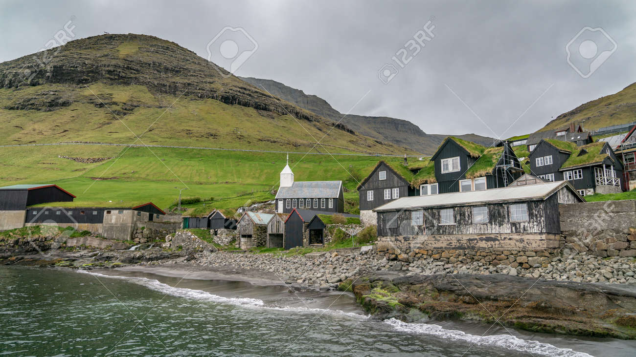 Bour, Faroe Islands - August 2019: Typical nordic village overlooking a fjord surrounded by green mountains . - 164356076