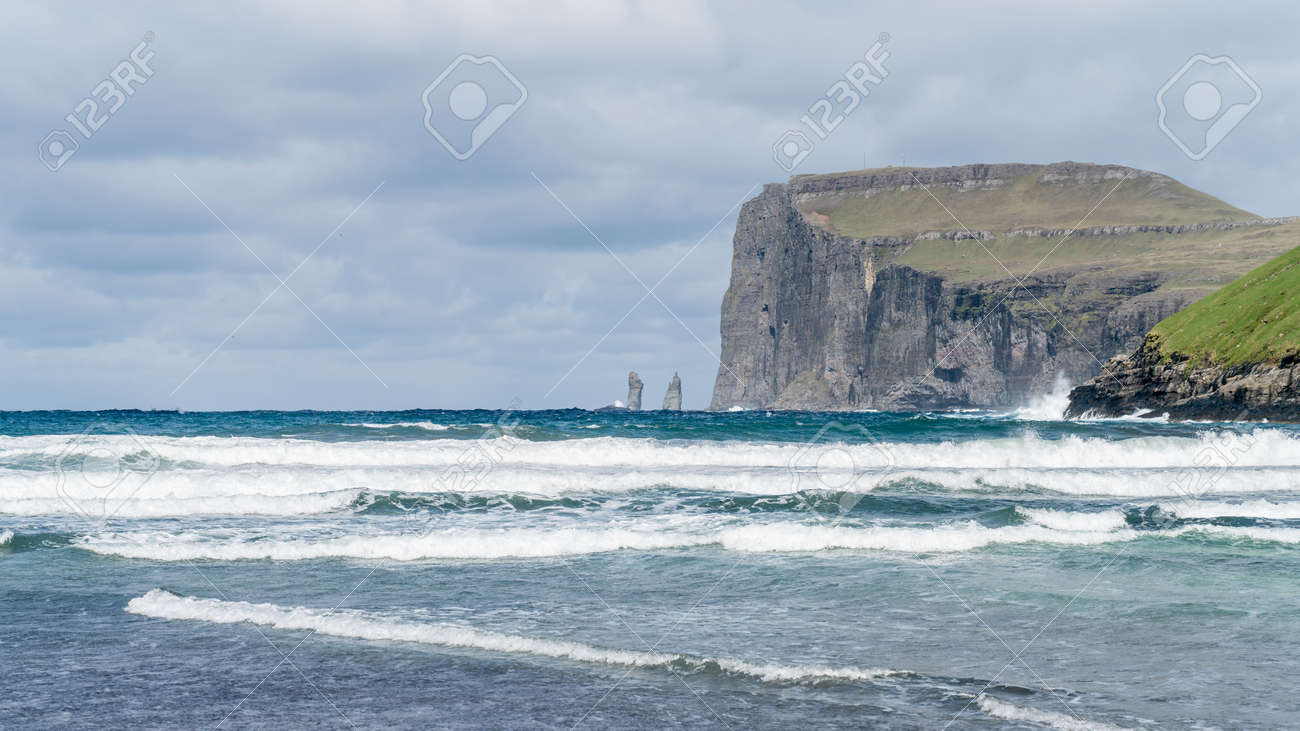 Risin and Kellingin rocks as seen from Tjornuvik bay with waves hitting the shore on Streymoy on the Faroe Islands, Denmark, Europe - 164385892