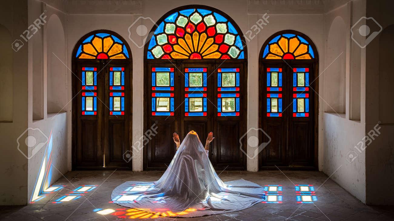 Kashan, Iran - May 2019: Unidentified Iranian woman in chador hijab praying inside Tabatabaei Natanzi Khaneh Historical House - 164356043